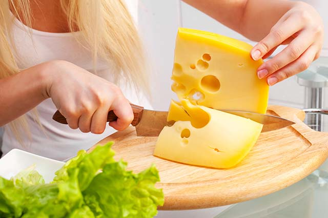 Девушка режет сыр