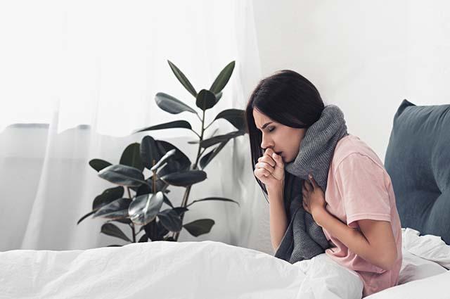 Девушка с больным горлом лежит в кровати