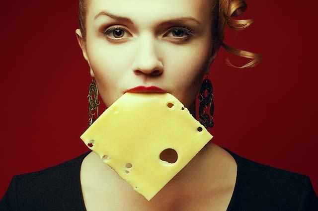 Девушка зубами держит ломтик сыра