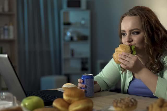 Девушка за компьютером ест